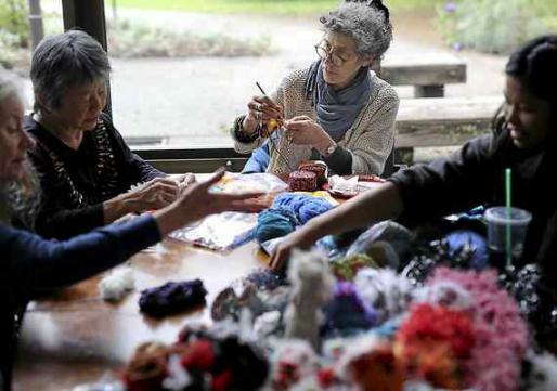 Stacey Grant, center, joins students and Santa Cruz locals at Porter College at UC Santa Cruz on Saturday afternoon to crochet the UC Santa Cruz Satellite Reef. The project aims to raise awareness about ocean health and collective action. (Kevin Johnson -- Santa Cruz Sentinel)