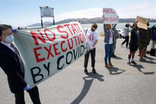 """Protestors hold a banner which says """"No State Execution by Covid-19"""""""